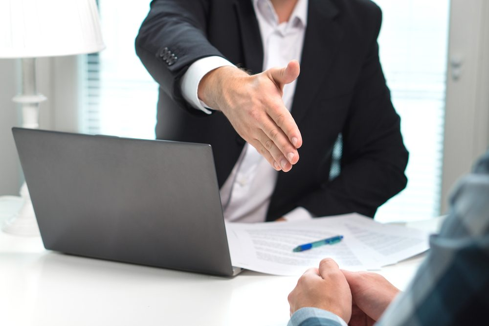 Business man offer and give hand for handshake in office. Successful job interview. Apply for loan in bank. Salesman, bank worker or lawyer shake for deal, agreement or sale. Increase of salary.