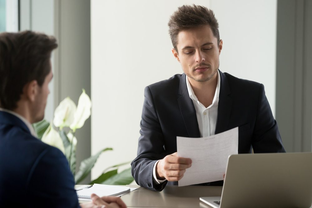 Company leader reading contract, attentively studying text of agreement, doubting some deal conditions while sitting at desk with business partner. Pensive CEO examining financial document or plan