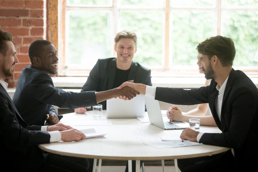 Smiling african american welcoming on board business partner by handshake at corporate meeting. Company team cheerfully greeting new colleague. Partnership, coworking, cooperation, negotiation concept