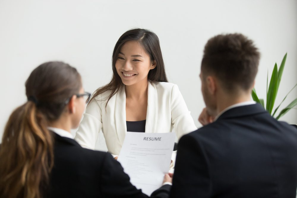 Confident millennial asian applicant smiling at job interview, happy beautiful chinese candidate or self-assured seeker being interviewed by hr managers, good performance and first impression concept