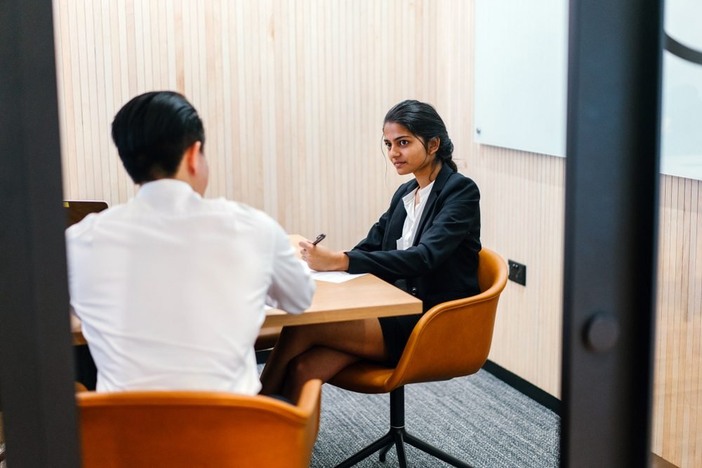 Portrait of a young, attractive and confident Indian Asian woman having a meeting with a Chinese man in a meeting room. She is either having an interview or is giving a performance review.