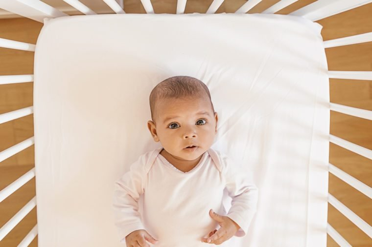 Cute Baby Girl Lying in the Crib. At home