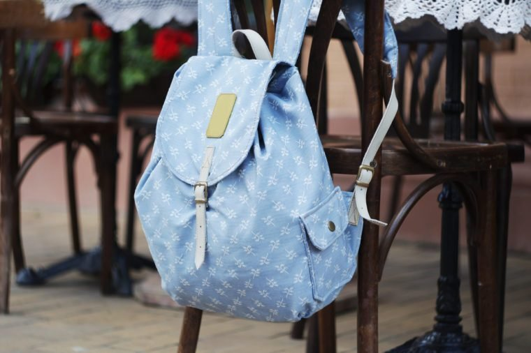Backpack on the chair of cafe. Blue with brown and white pattern bag. Hand made backpack for travelers.