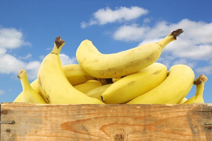 fresh bananas in a wooden crate against a blue sky with clouds on a white background
