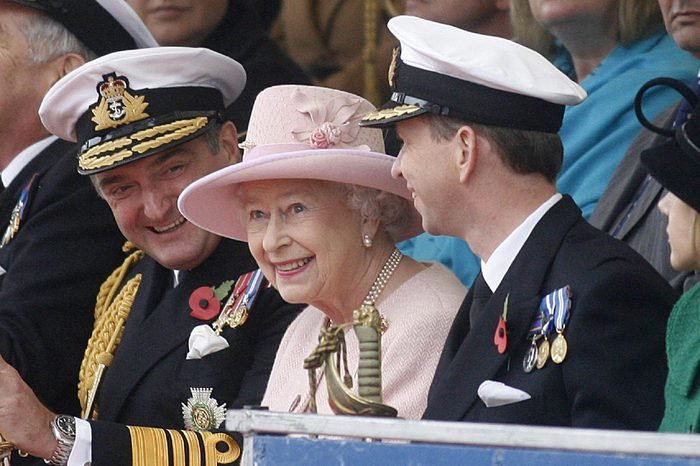 Queen Elizabeth II smiles as she sits with Captain Jerry Kyd (R) Commanding officer of HMS Ark Royal and Admiral Sir Trevor Soar Commander-in-Chief Fleet (L).