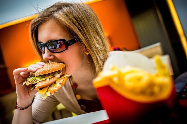 BUDAPEST, HUNGARY, April, 2013: Young woman eating a Big Mac hamburger menu in a McDonald's restaurant. Illustrative editorial.