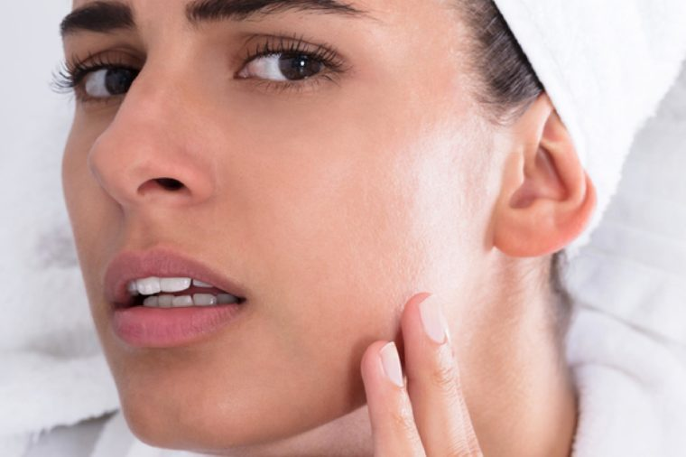 Close-up Of Young Woman Looking At Pimple And Squeezing On Forehead