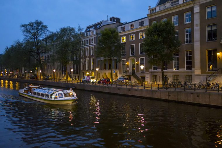 Canal cruise in the city of Amsterdam by night - AMSTERDAM / THE NETHERLANDS - JULY 19, 2017
