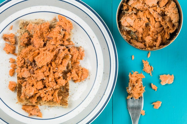 Tinned Salmon on Toast or Toasted Bread Against a Blue Background