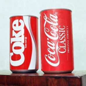 Cans of New Coke and Coca-Cola Classic are on display during a news conference in Atlanta. New Coke's sweeter formula was a marketed as an improved replacement for the flagship soda, but the outcry was immediate and sustained. Coke tried to sell both versions for awhile, but eventually reverted to