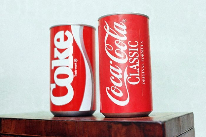 """Cans of New Coke and Coca-Cola Classic are on display during a news conference in Atlanta. New Coke's sweeter formula was a marketed as an improved replacement for the flagship soda, but the outcry was immediate and sustained. Coke tried to sell both versions for awhile, but eventually reverted to """"Coca-Cola Classic"""