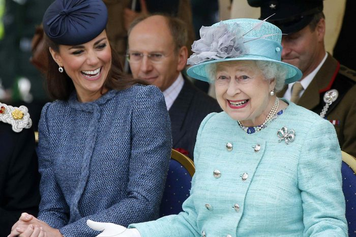 Catherine Duchess of Cambridge (L) laughs as Queen Elizabeth II gestures while they watch part of a children's sports event during a visit to Vernon Park in Nottingham