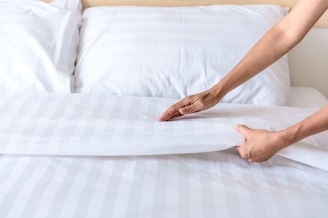 Hand set up white bed sheet in room