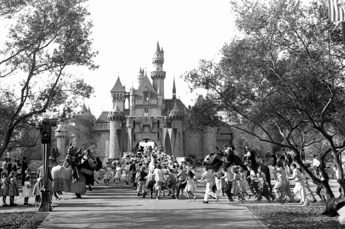 Children sprint across a drawbridge and into a castle that marks the entrance to Fantasyland at the opening of Walt Disney's Disneyland in Anaheim, Calif. Fantasyland had been closed until late in the day