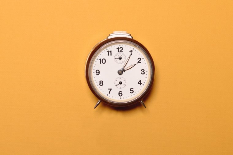 Vintage brown alarm clock on yellow ocher background - Trendy minimal flat lay concept