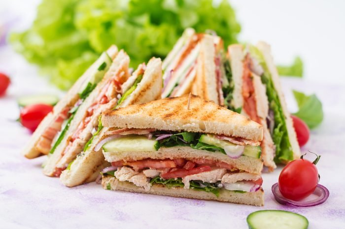 Club sandwich with chicken breast, bacon, tomato, cucumber and herbs