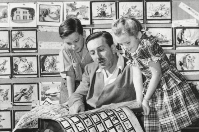 """December 27, 1946 - Walt Disney shows 2 young actors, Bobby Driscoll (left), and Luana Patten (right) the storyboards for his new production, """"Song of the South."""""""