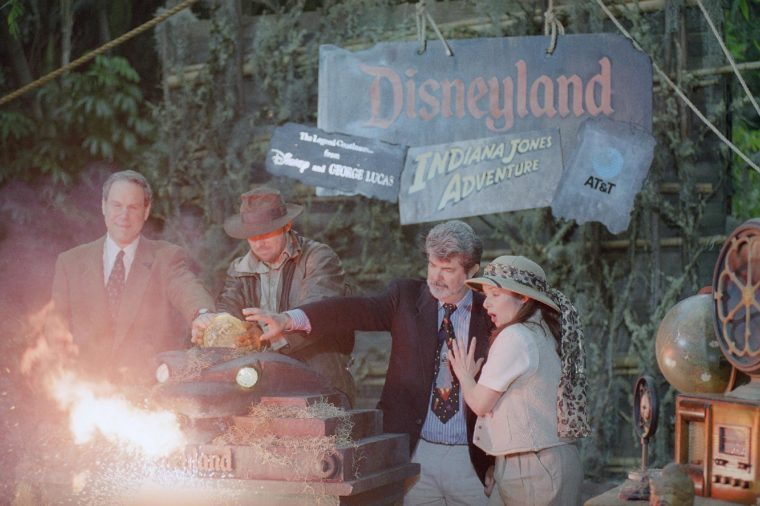 Disney chief Michael Eisner, left, and director George Lucas, second from right, are assisted by actors portraying Indiana Jones and Jones' assistant, as they officially open the Indiana Jones adventure attraction at Disneyland in Anaheim, California