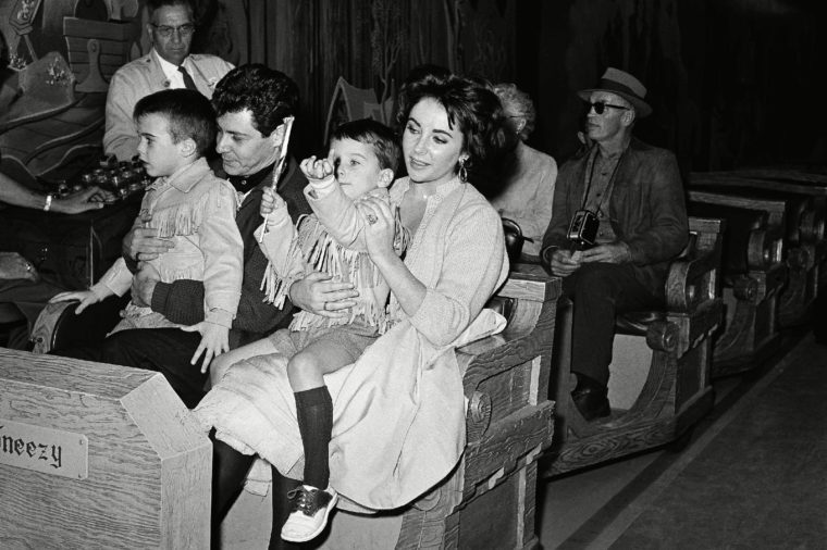 Elizabeth Taylor and boy friend Eddie Fisher hold her children by her marriage to actor Michael Wilding as they begin one of the fantasy rides during an outing at Disneyland, Anaheim, Calif., on . The boys are Michael (left), 6, and Christopher, 4