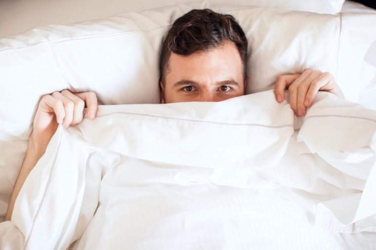Portrait of a young man pulling the sheets of his bed up and peeking over them