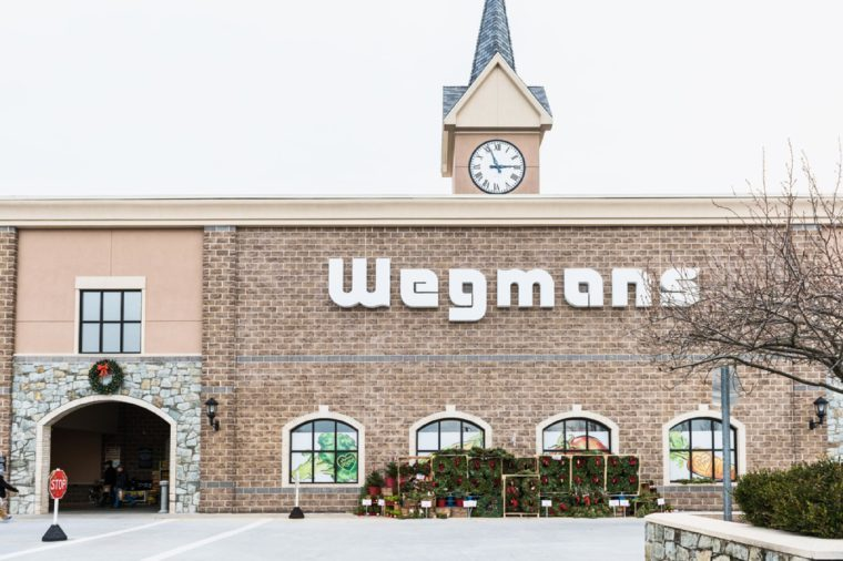 Fairfax, USA - November 30, 2016: Wegmans grocery store facade and sign with people and Christmas wreath decorations
