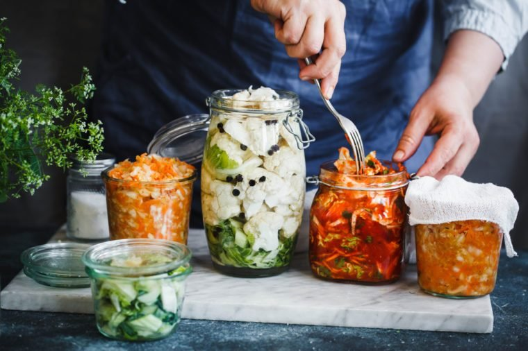Fermented preserved vegetarian food concept. Cabbage kimchi, broccoli marinated, sauerkraut sour glass jars over rustic kitchen table. Canned food concept.