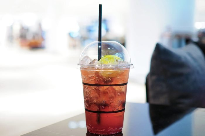 A refreshing plastic glass of iced lemon tea mixed with blueberry on the table. Selective focus.