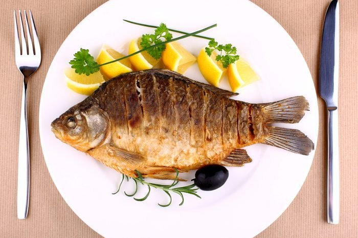 Fried fish on white plate with fork and knife, closeup