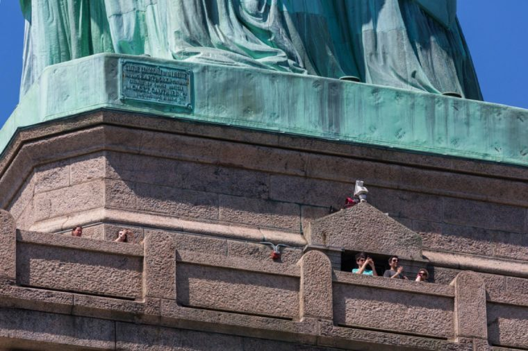 NEW YORK CITY, USA – JULY 15, 2013: A tourist at the foot of the Statue of Liberty on the observation deck while visiting the museum on a summer sunny day.