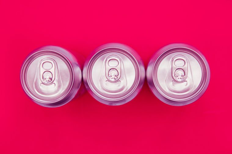 Silver metal energy drinks cans on bright pink background