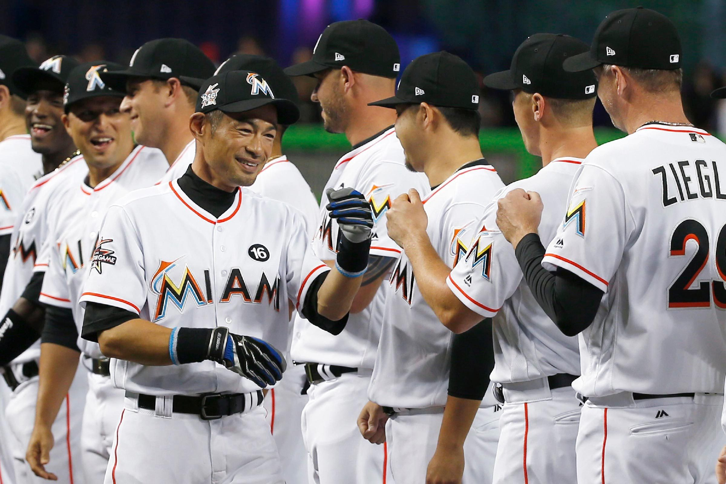 Miami Marlins' Ichiro Suzuki, of Japan, greets teammates during team player introductions before the start of a baseball game against the Atlanta Braves, in Miami