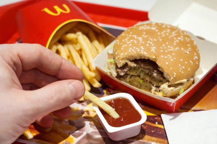 Minsk, Belarus, January 8, 2018: Man is eating at McDonald's restaurant.