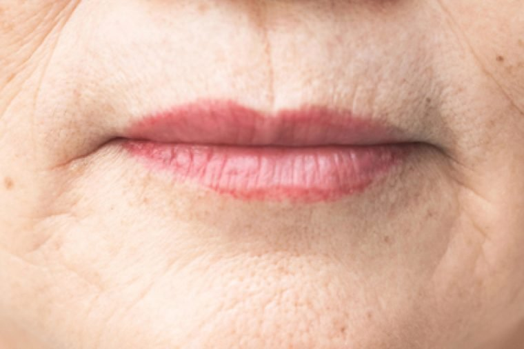 wrinkled and lines of old asian woman skin texture in closeup selective focus