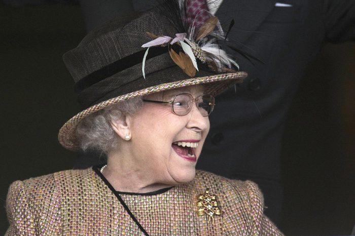 Queen Elizabeth II and John Warren celebrate as the Queen's horse Sign Manual wins the Dreweatts Handicap Stakes