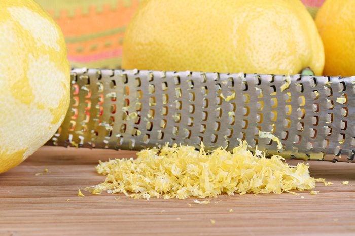 Lemon zest with zester behind zest. Macro with selective focus on lemon zest.