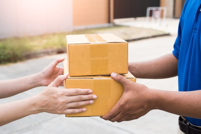 Women hands receiving package from delivery man.