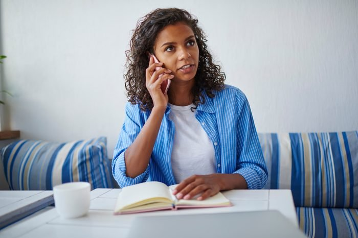 Serious african american woman having consultancy with service operator talking on mobile phone on free time,pensive dark skinned student banking through telephone conversation sitting in cafe