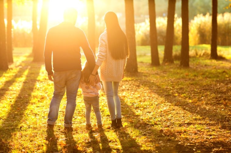 family with little daughter spend fun time in autumn park at sunset, back view