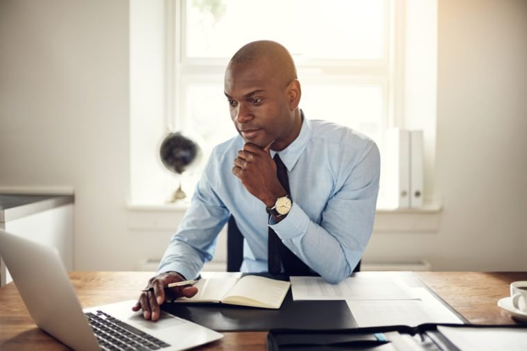 Young African business executive wearing a shirt and tie sitting at his desk in an office working online with a laptop