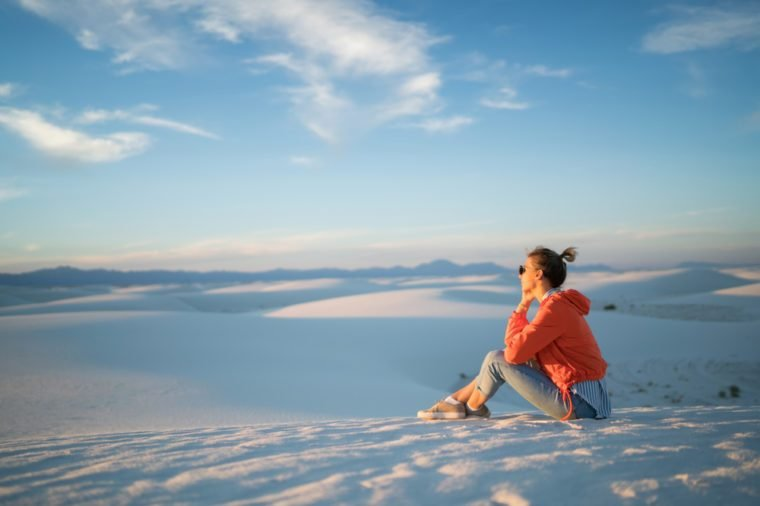 Pensive young woman observing beautiful landscape of white dunes on skyline horizon in desert during summer trip, female traveler sitting looking away at scenic view of natural landmark in New Mexico