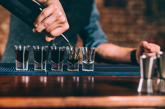 Bartender pouring strong alcoholic drink into small glasses on bar counter