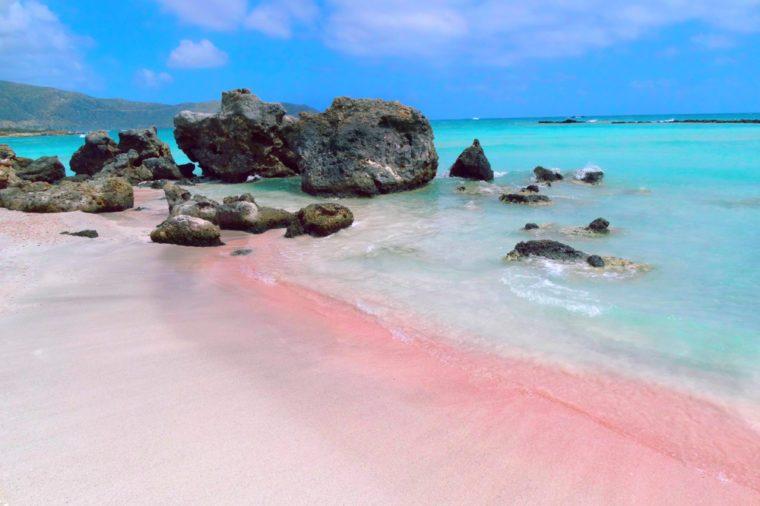 beach coast with pink sand sea landscape and mountains on Crete island
