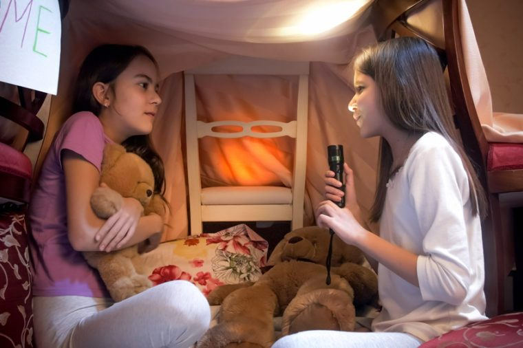 Girl with flashlight telling scary story to her friend