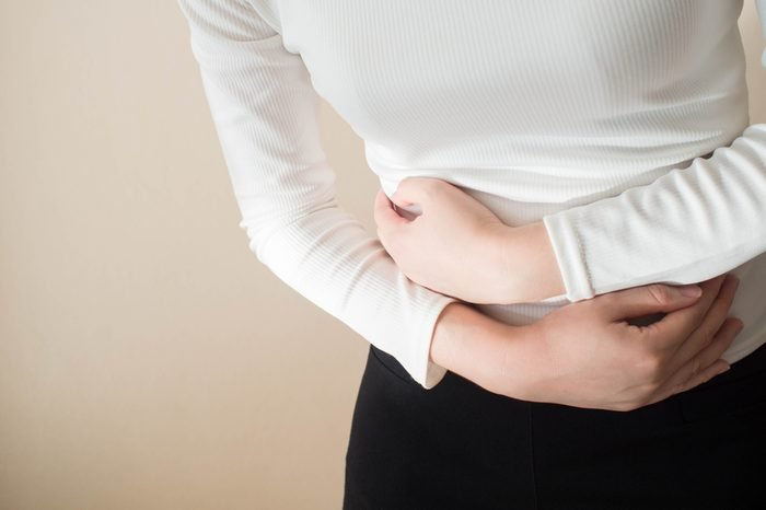 Young female suffering form stomach ache on gray background w/ copy space. Causes of abdominal pain include menstruation pain, gastritis, stomach ulcer, food poisoning, diarrhea or IBS. Close up.