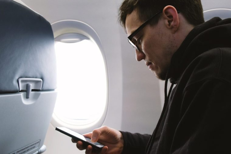 Man in glasses uses a smartphone on a plane, sitting at the window, 4k.