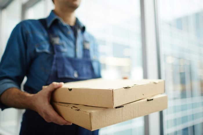 Two boxes with fast food being carried by delivery man in uniform for one of clients
