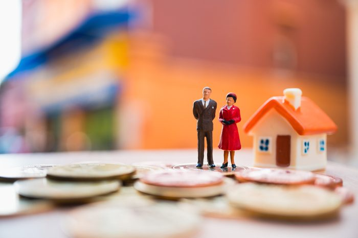 Miniature people, man and woman standing with colorful house and stack coins using as business and family life concept