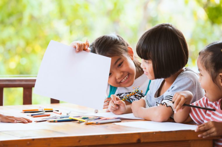 Group of asian children drawing and painting with crayon together with fun