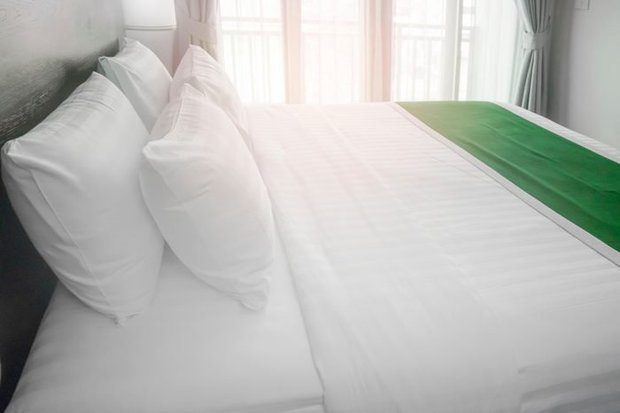 made up bedding in modern comfortable bedroom with clean white bed sheet and pillow with light from glass window