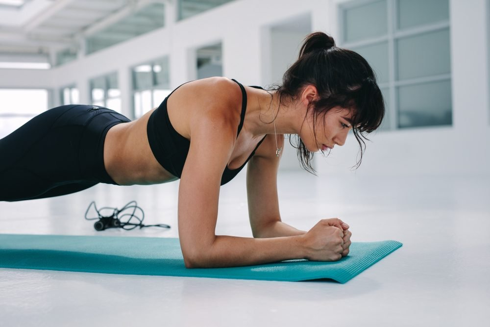 Muscular young woman doing plank exercise training at gym. Female exercising in fitness studio.